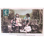 French Tinted RPPC, The New Doll, 4 Little Girls in a Garden With a French Bisque Doll, Real Photo Postcard Postmarked 1911
