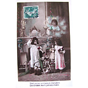 Christmas Postcard, Cherub, Little Boy and Girl, Dolls and Toys, Hand Tinted French Real Photo Postcard Postmarked 1909