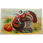 Antique Thanksgiving Postcard with Boy Holding Flag Riding a Turkey
