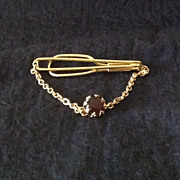 Gold tone tie bar with chain and brown glass stone