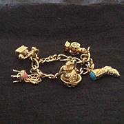 Gold tone charm bracelet with 5 Avon charms