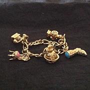 Gold tone charm bracelet with 5 Avon charms