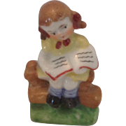 Occupied Japan figurine of little girl on a bench with a book
