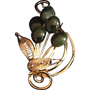 Vintage gold tone stylized floral metal pin with green flowers.