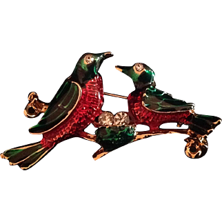 Bright red and green enamel birds with a nest