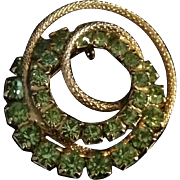 Vintage gold tone pin with concentric swirls and prong set green rhinestones