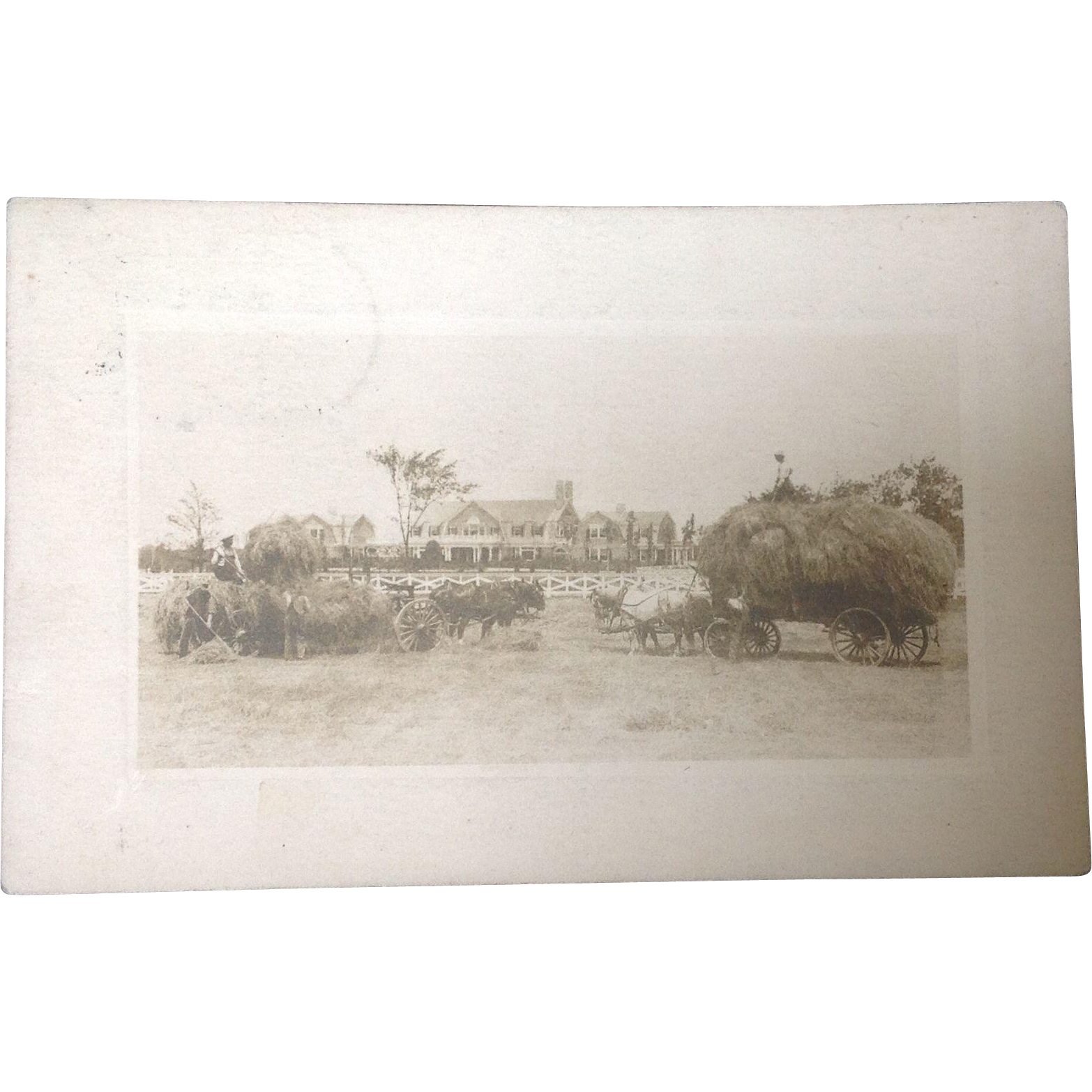 Real Photo Postcard with farmers and hay wagons in front of a beautiful farmhouse