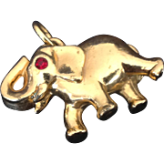 Gold tone elephant charm with red rhinestone eye and upraised trunk