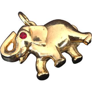 Gold tone elephant charm with red rhinestone eye and upraised trunk