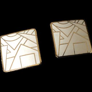 White enamel and gold tone geometric design square clip earrings.