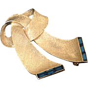 Lisner gold tone ribbon pin with deep blue channel set rhinestones