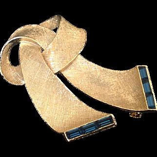 Lisner gold tone ribbon pin with deep blue channel set rhinestones