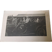 Real Photo Postcard of Man, Woman and Dog in Automobile with Sad message on the back