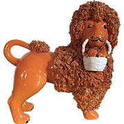 Antique Pottery Figure of a Poodle Holding a Basket of Fruit with Orange Glaze