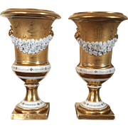 Pair Antique Early 19th century Locre Old Paris Porcelain Vases or Urns with Bisque Floral Swags on Two Tone Gold Ground with Trophies and Lion Mask Handles