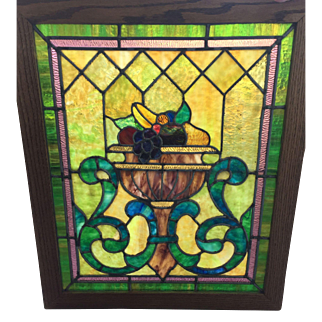 One of a matched pair of antique stained glass window featuring basket of fruit