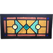 One of a matched pair of stained glass transom windows