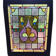 One of a matched pair of antique stained glass windows
