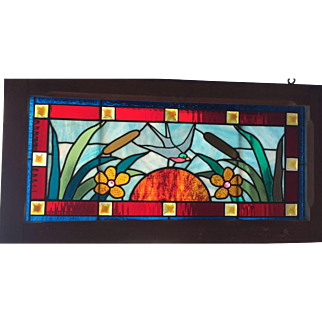 Antique stained glass transom window featuring bird and the setting sun