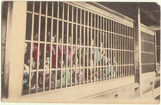 Japanese Prostitutes behind a Fence. Tinted Postcard