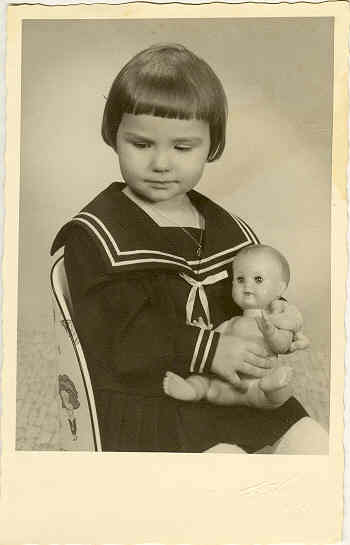 b/w Photo of Girl in Sailors Suite embracing a Doll