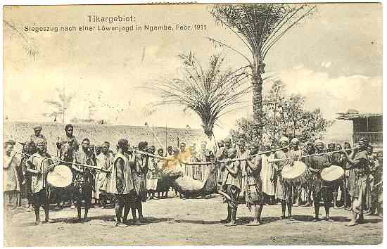 1911: Lion Hunting: African Hunters celebrating after the Hunt. Nintage Postcard.