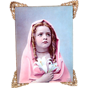 Antique Ullman Mfg Co glass tinted print solemn young girl with long ringlets holding lilies pink cape dated 1900