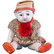 Tiny 2.5 inch all bisque doll wearing jester clown costume cap and knit shirt red pom pom made in Japan side glancing eyes