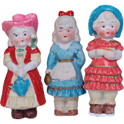 Three all bisque immobiles dolls little girls in sweet costumes hair bows and bonnets holding watering can purse book Made in Japan 2.25 inches