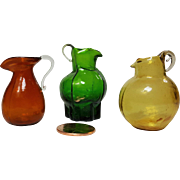 Three miniature blown glass handled pitchers doll house accessories amber emerald and gold glass  1.5 inch or less