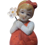 German All Bisque Girl Doll Holding Flower