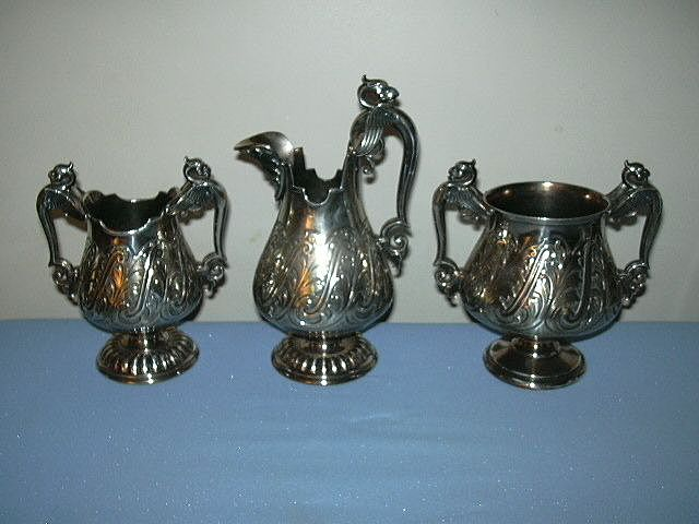 James W Tufts Silver Quadruple Plate 3Pc Creamer Syrup Set With Face Mythological & Winged Serpents