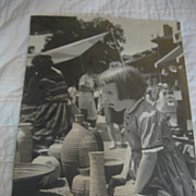Vintage Photograph of  Little Girl Looking in awe of Pottery