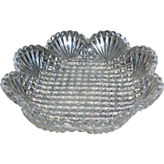 Vintage Pressed glass candy dish with a saw tooth edge and scalloped and block button design motif.
