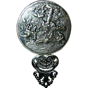 Pewter or spelter, small, pocket mirror with orignal beveled mirror and having a pastoral, community, motif....very charming!
