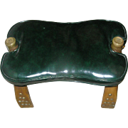 Camel back stool with a leather-like cushion of dark, dark, dark, green, excellent condition, brass detail