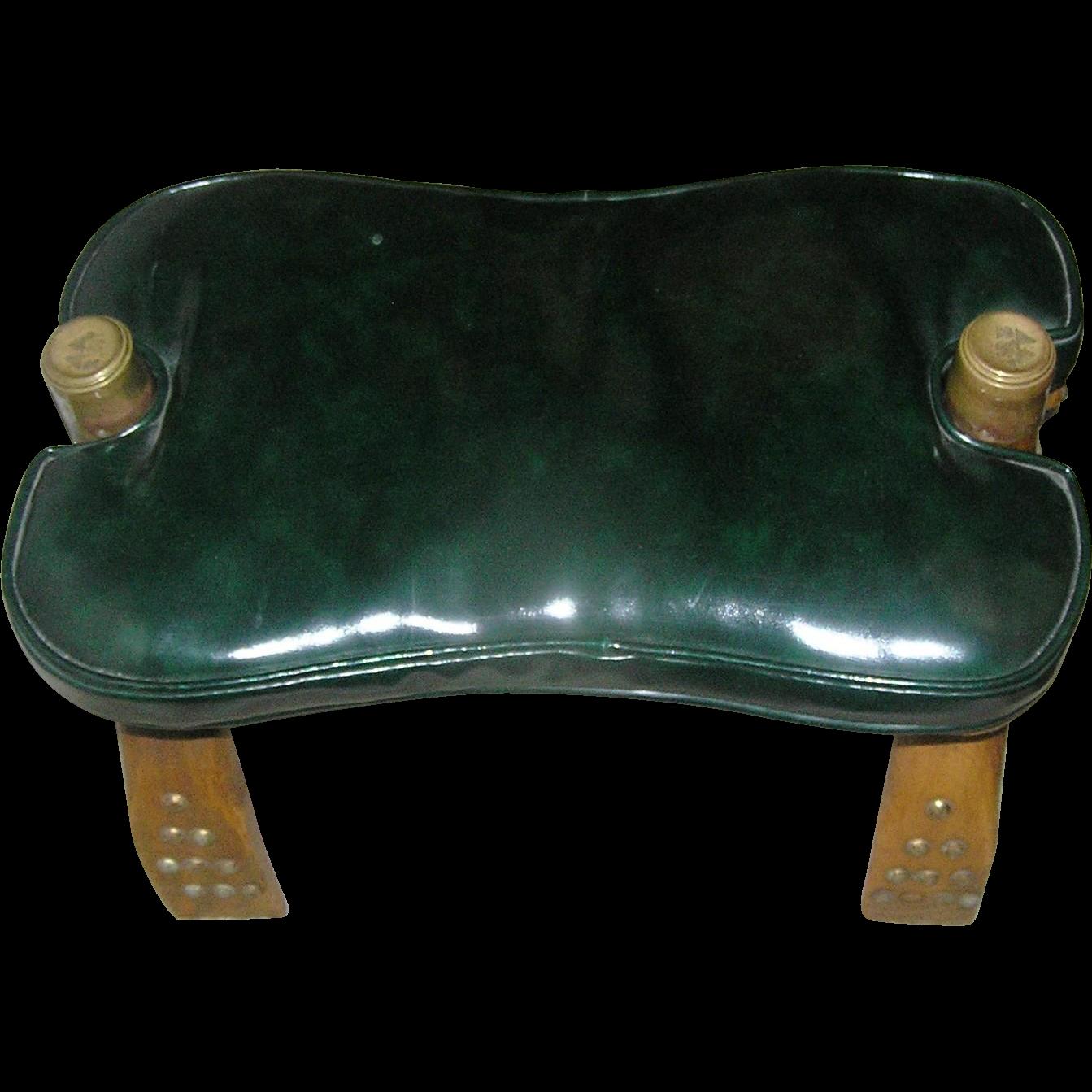 Camel back stool with a leather-like cushion of dark, dark ...