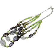 Chicoe's necklace of three strands of plastic and crystal beads