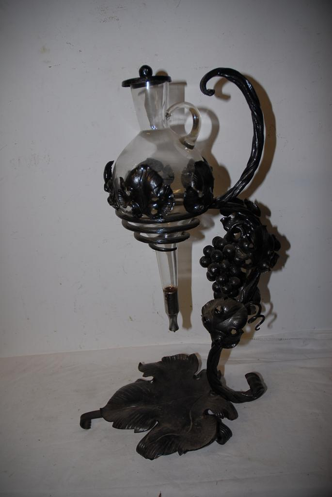 An Old Handmade Wrought Iron Wine Bottle Holder made out scrolled branches, leaves and bunch of grapes