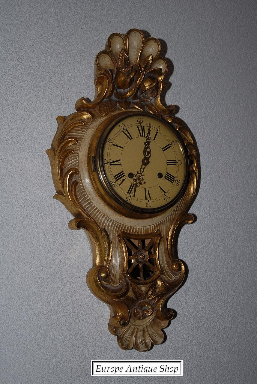 A carved gilt wooden cartel wall clock from