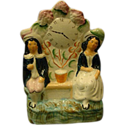 Staffordshire England antique figurine couple sitting by clock