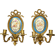 French porcelain and bronze pair of cupid wall sconces
