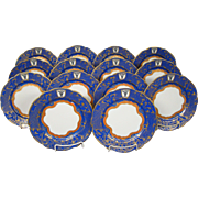 Ornate gilded blue set fourteen salad plates bull's head crown mark scalloped edge