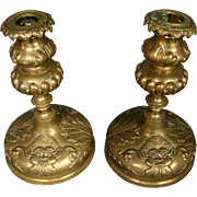 Antique pair brass candlesticks faces dolphins coat of arms
