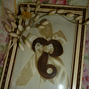 Adorable antique French framed lock of hair with cream silk bow