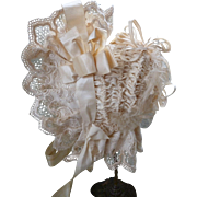 Extravagant frothy antique French doll's cream ruched bonnet : silk ribbons : bows : lace : rosettes