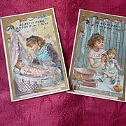 2  pretty 19th C. French shop trade cards : little girls with dolls : Au Petit Paris Ottot Fils Caen