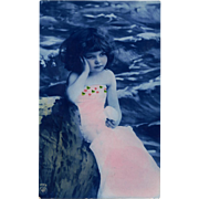 NPG Real Photo Postcard of Girl in Pink Wrap Against Delft Blue Background 1909