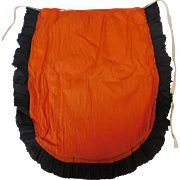Crepe paper apron depicting orange and black Halloween colors 1922 – 1935