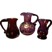 Three Clevenger Amethyst Pitchers